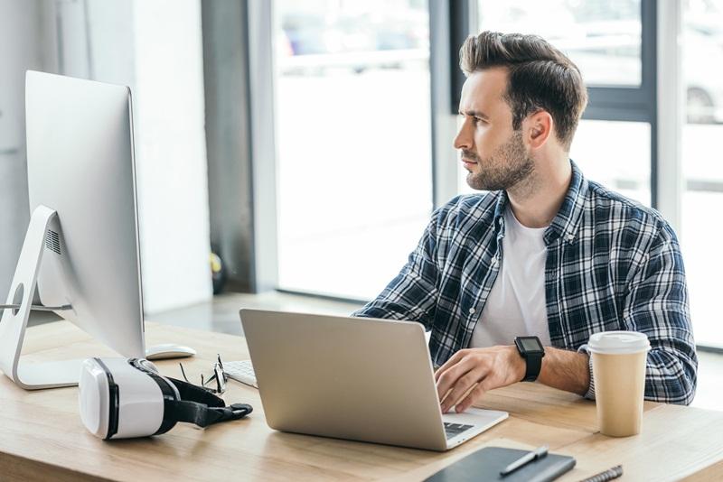 Homem, em um computador portatil, verificando a relação entre uma boa hospedagem e um bom SEO para o seu site
