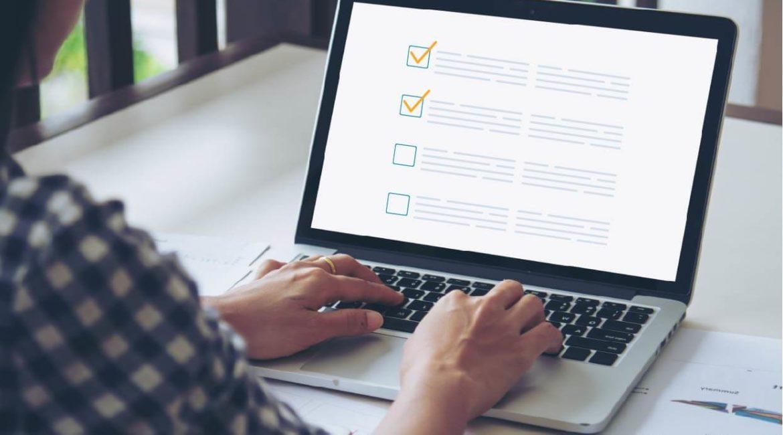 Pessoa de perfil fazendo sua checklist de SEO no computador/laptop.